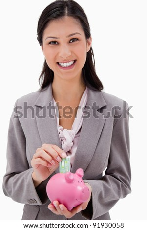 Businesswoman putting money into piggy bank against a white background - stock photo