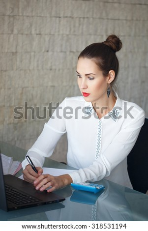 Businesswoman reading data and write to black paper in office - stock photo