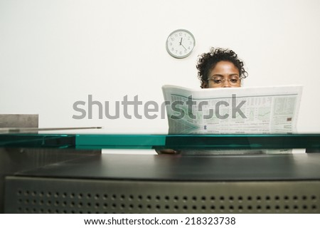 Businesswoman reading newspaper - stock photo