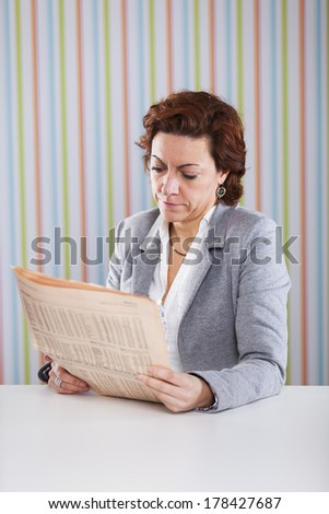 Businesswoman reading the newspaper at the office
