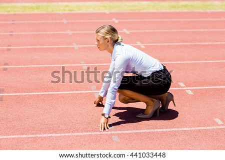 Businesswoman ready to run on running track on a sunny day