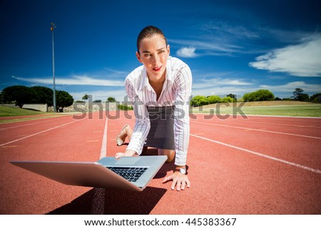 Businesswoman ready to run on running track with a laptop