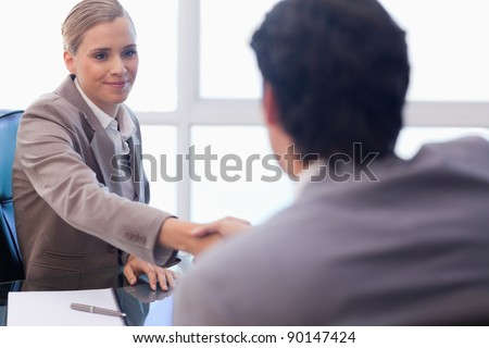 Businesswoman receiving a customer in her office - stock photo