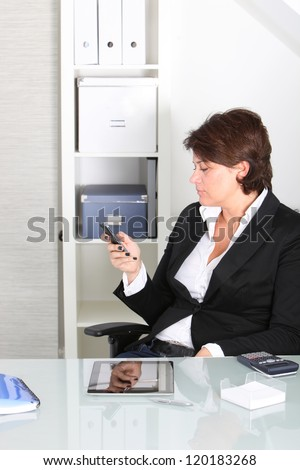 Businesswoman receiving a message on her mobile sitting in her office chair reading the text on the screen with a tablet and calculator in front of her - stock photo