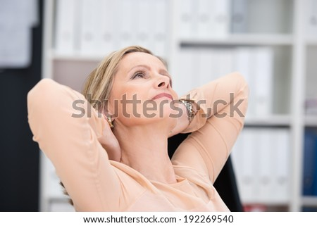 Businesswoman relaxing at the office reclining back in her chair with her hands clasped behind her head staring dreamily up into the air - stock photo