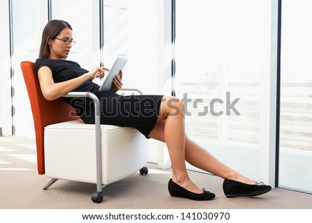 Businesswoman Relaxing With Digital Tablet During Break - stock photo
