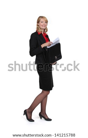 Businesswoman removing document from case - stock photo