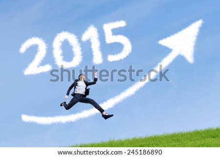 Businesswoman running on the meadow with upward arrow and number 2015 - stock photo