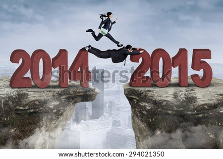 Businesswoman runs above her partner through a gap from number 2014 to 2015 - stock photo