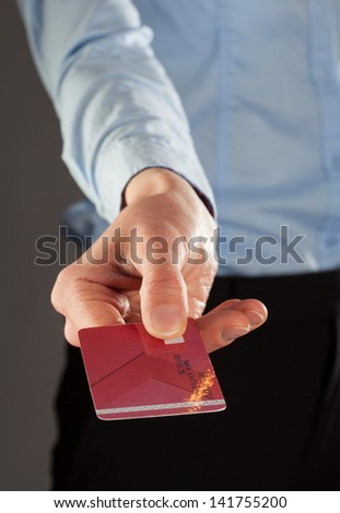 Businesswoman's hand giving credit card to you, closeup shot - stock photo