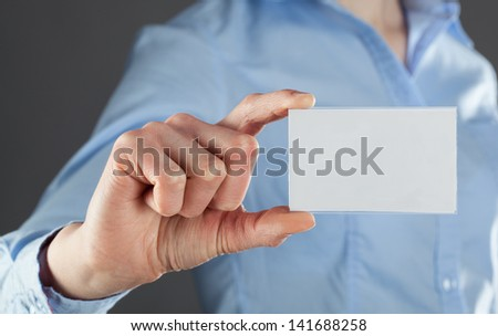 Businesswoman's hand showing business card - stock photo