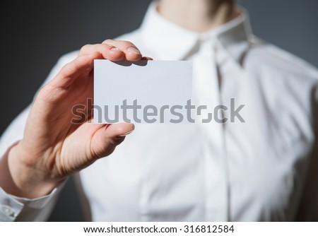 Businesswoman's hand showing business card on dark background - stock photo