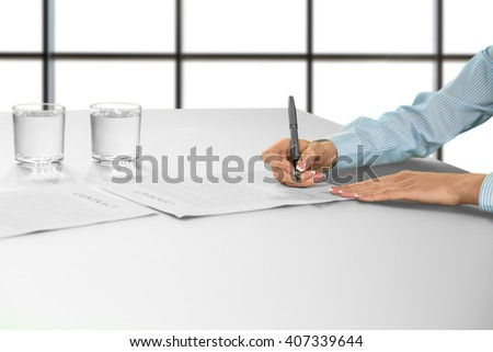 Businesswoman's hand signing document. Female signs contract at desk. Employment procedure on white background. Think everything over. - stock photo