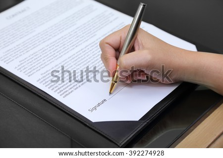 businesswoman's hand signing the contract with pen - stock photo