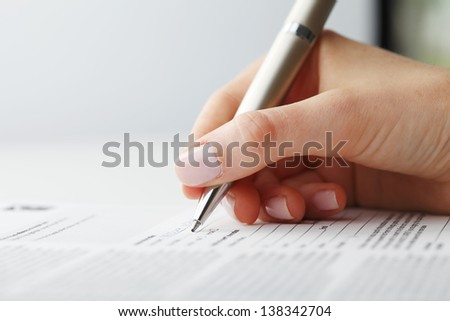 Businesswoman's hand with pen completing personal information on a form - stock photo