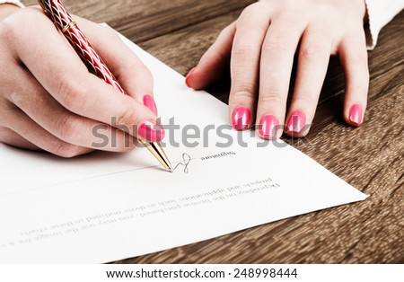 Businesswoman's hand with pen signing a contract.  - stock photo