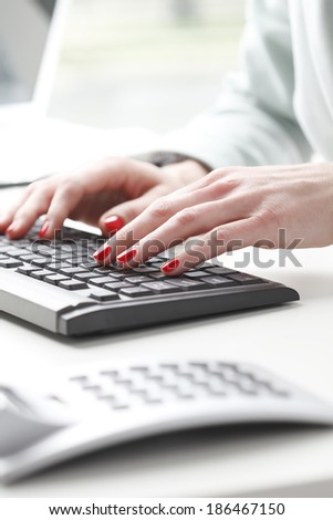 Businesswoman'?s hands touching computer keyboard and analyzing data. Small business.