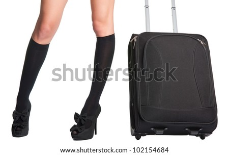 Businesswoman s legs in high stockings and high heels, holding a black suitcase - stock photo