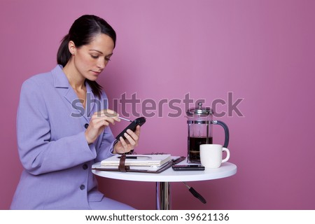 Businesswoman sat at a cafe table entering information on her personal organizer. - stock photo