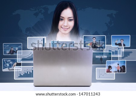 Businesswoman searching online pictures from her laptop on blue background