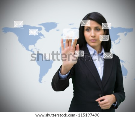 Businesswoman selecting holographic email symbol against world map background - stock photo