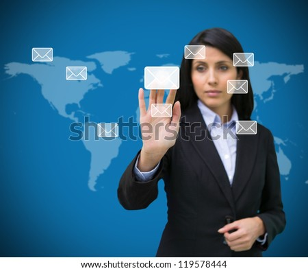Businesswoman selecting holographic email symbol from many against blue world map - stock photo