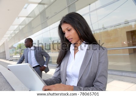 Businesswoman sending email with electronic tablet - stock photo
