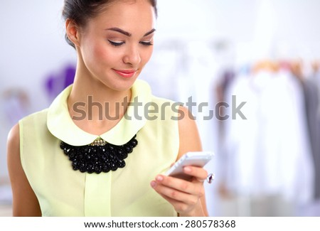 Businesswoman sending message with smartphone in office  - stock photo