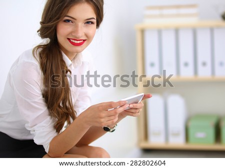 Businesswoman sending message with smartphone in office. - stock photo