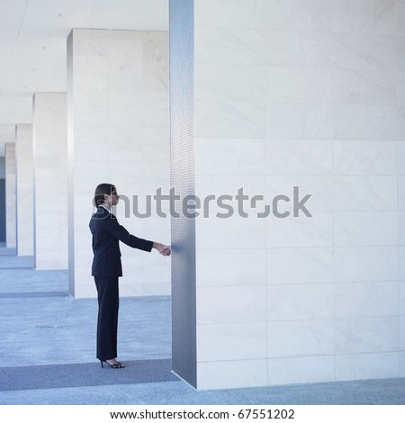 Businesswoman shaking hand behind wall
