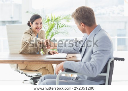 Businesswoman shaking hands with disabled colleague in an office - stock photo