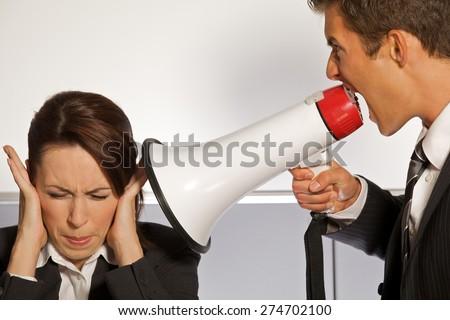 Businesswoman shouting at businessman through megaphone - stock photo