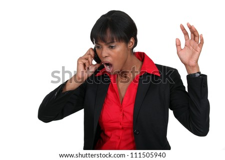 Businesswoman shouting down the phone - stock photo