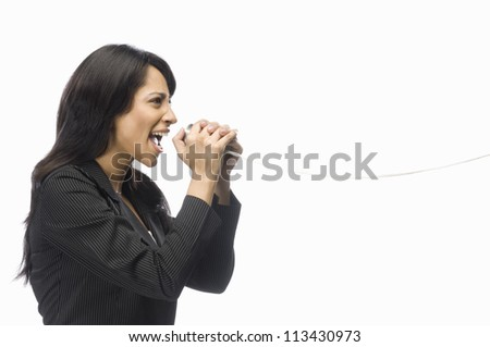 Businesswoman shouting in a tin can phone