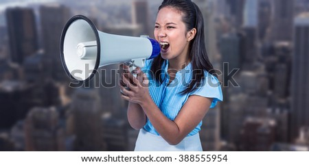 Businesswoman shouting into a megaphone against view of cityscape - stock photo