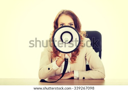 Businesswoman shouting with megaphone by a desk. - stock photo