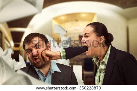 Businesswoman shouts at young businessman and beats him  - stock photo
