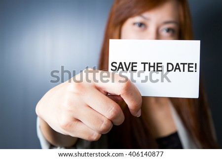 "Businesswoman show message ""SAVE THE DATE!"" on the card."