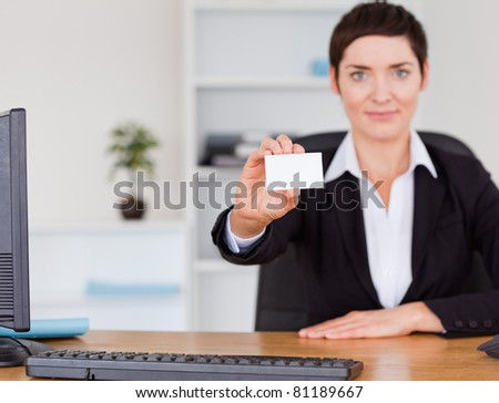 Businesswoman showing a blank business card in her office