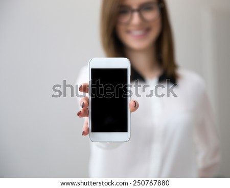 Businesswoman showing a blank smartphone screen. Focus on smartphone - stock photo