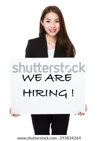 Businesswoman showing a board showing with we are hiring phrases  - stock photo