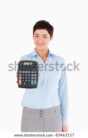 Businesswoman showing a calculator against a white background