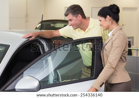 Businesswoman showing a car interior to her customers at new car showroom - stock photo