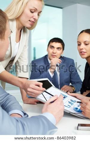 Businesswoman showing charts to colleagues - stock photo