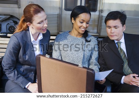 Businesswoman showing document from briefcase to two colleagues on train station platform, smiling