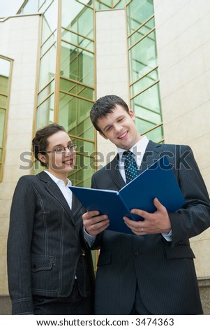 Businesswoman showing documents to her colleague holding the blue paper case outside the building with glassy walls