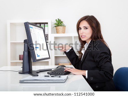 Businesswoman Showing Graph On Monitor In Office. - stock photo