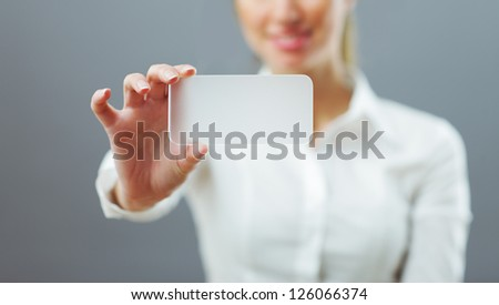 Businesswoman showing her business card. Shallow depth of field - focus on fingers and card. You can just add your text there. - stock photo