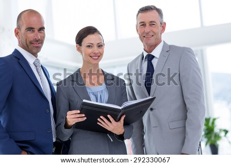 Businesswoman showing her notes to her colleagues and smiling at the camera