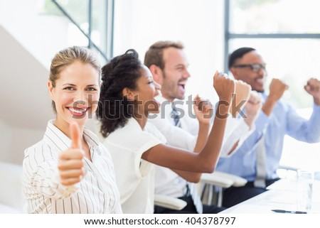 Businesswoman showing her thumbs up in office while team celebrating in background